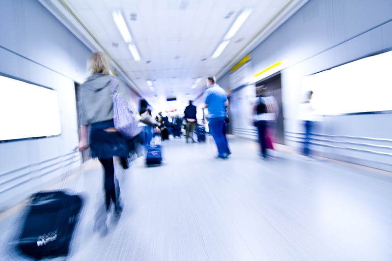 Crowd of people rushing through airport terminal toward boarding gates. Colour photograph.