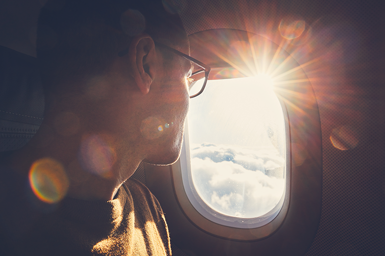 Individual looking through airplane window Drive Loyalty Through the Traveler Experience