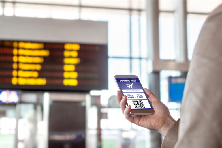 Close up of individual, in an aiport, holding up mobile phone displaying board pass