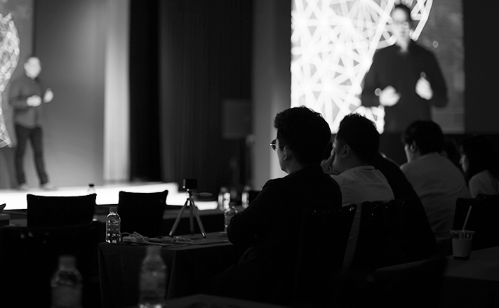 Individuals in an audience sat watching a presentation