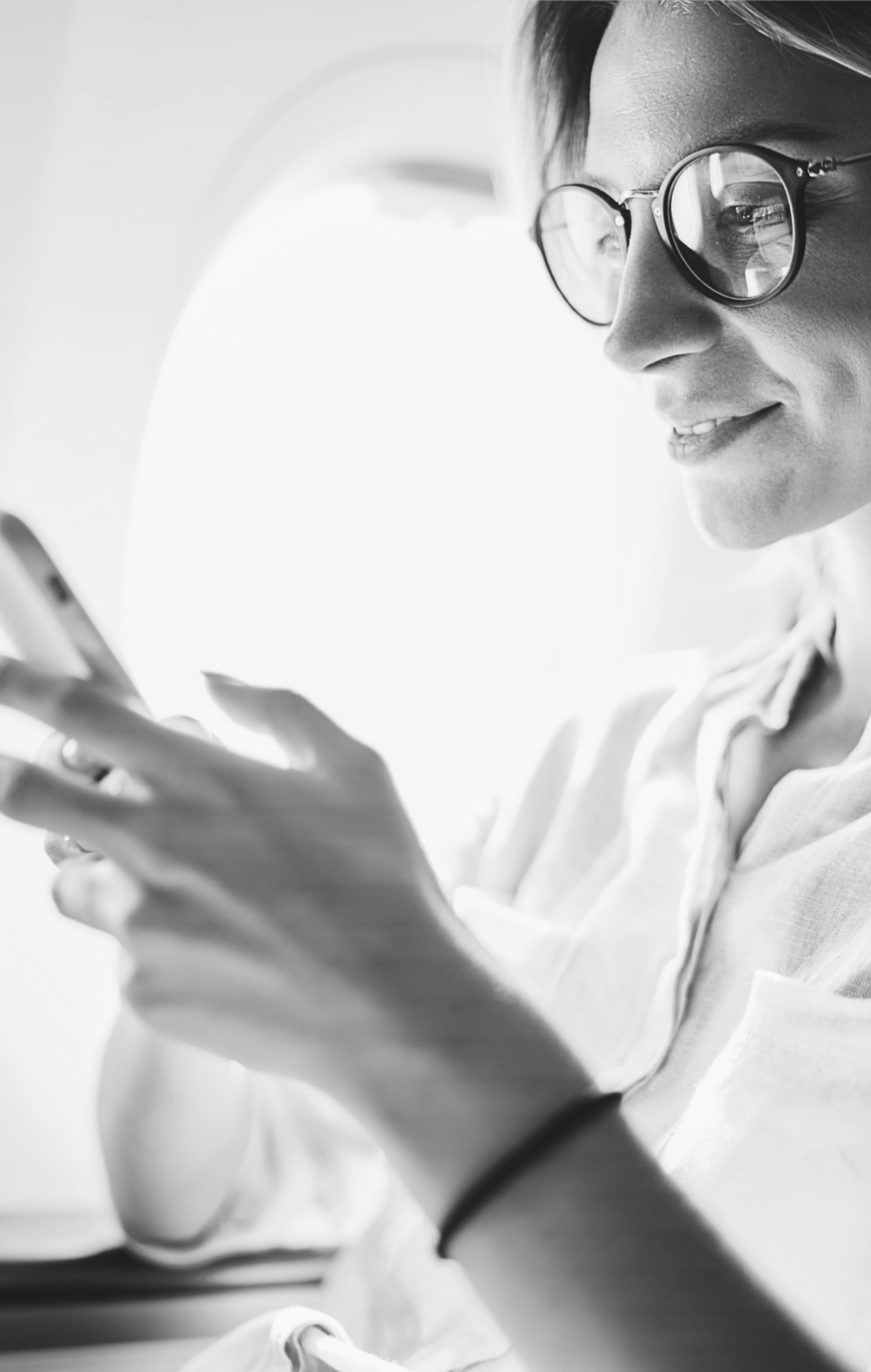 Close up of woman using a mobile device whilst sat on an airplane