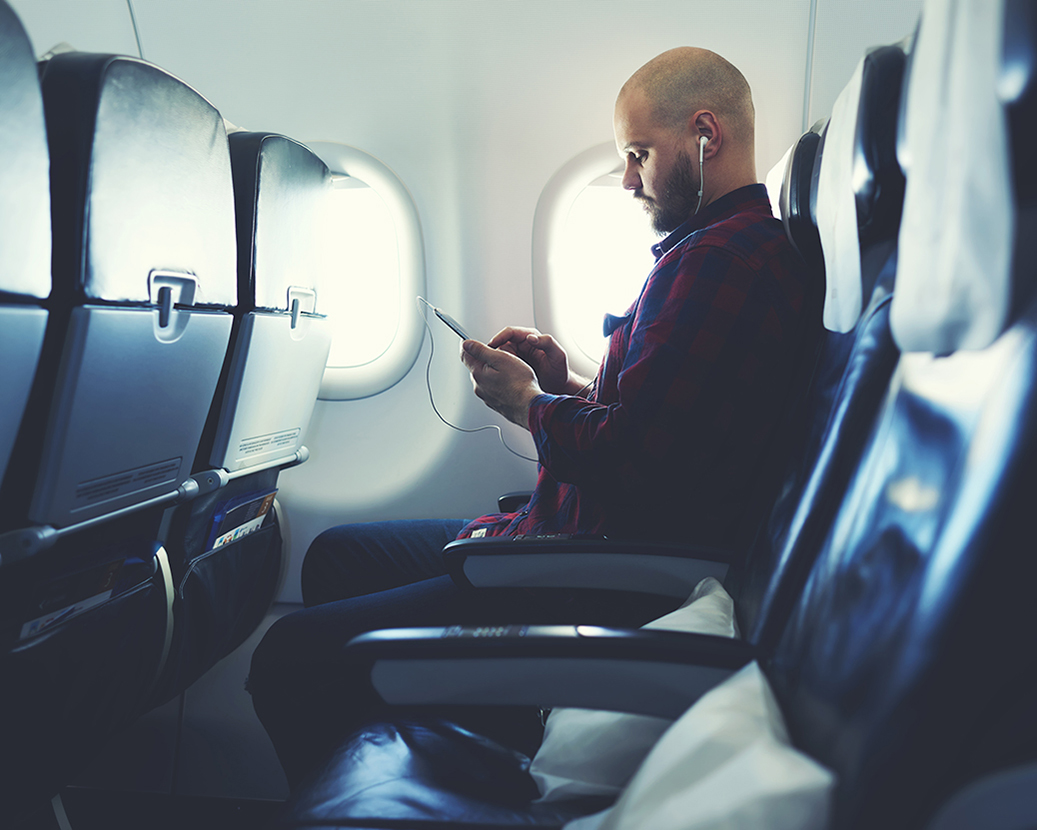 Man using device on plane
