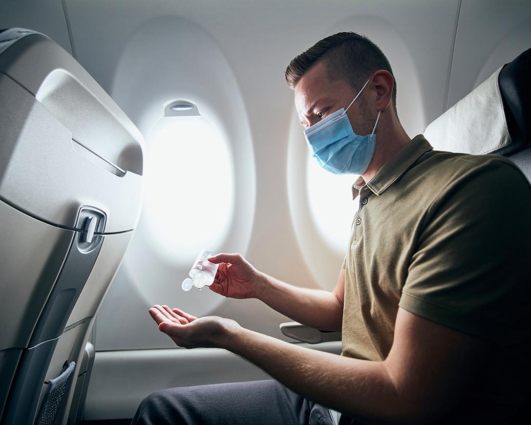airline passenger using hand sanitizer