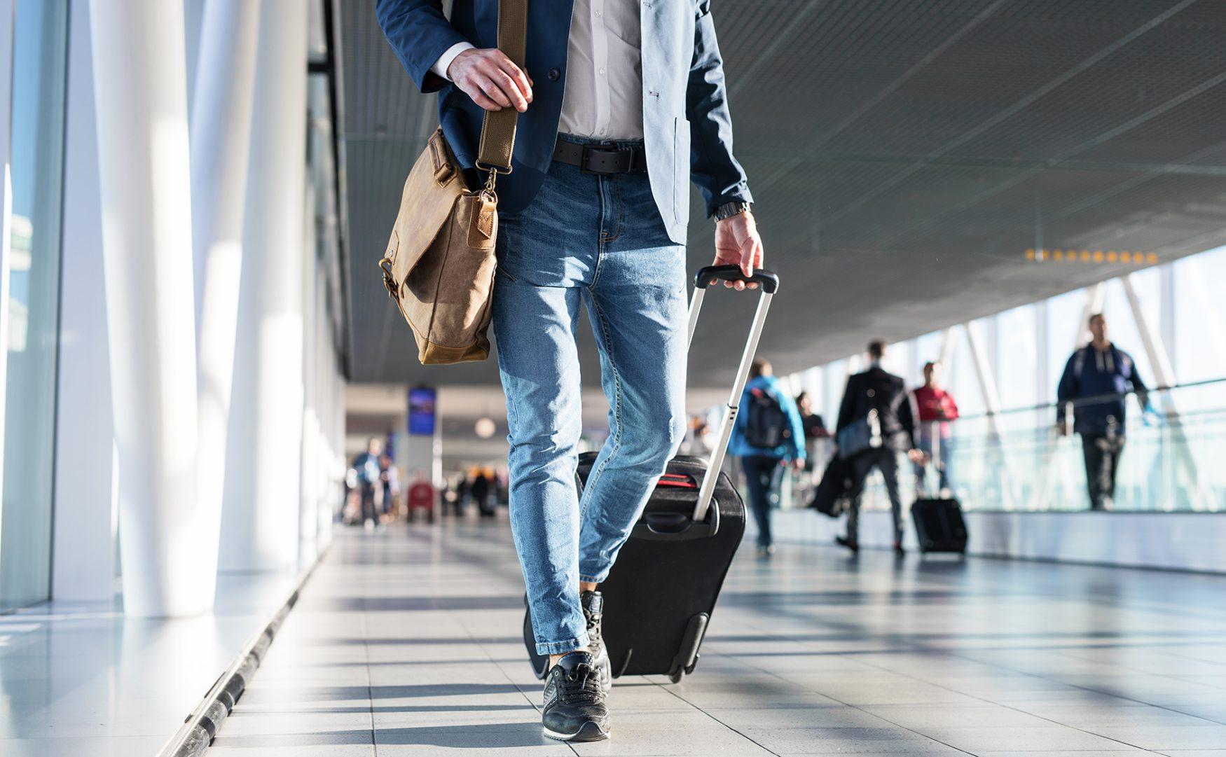 man walking through terminal with luggage