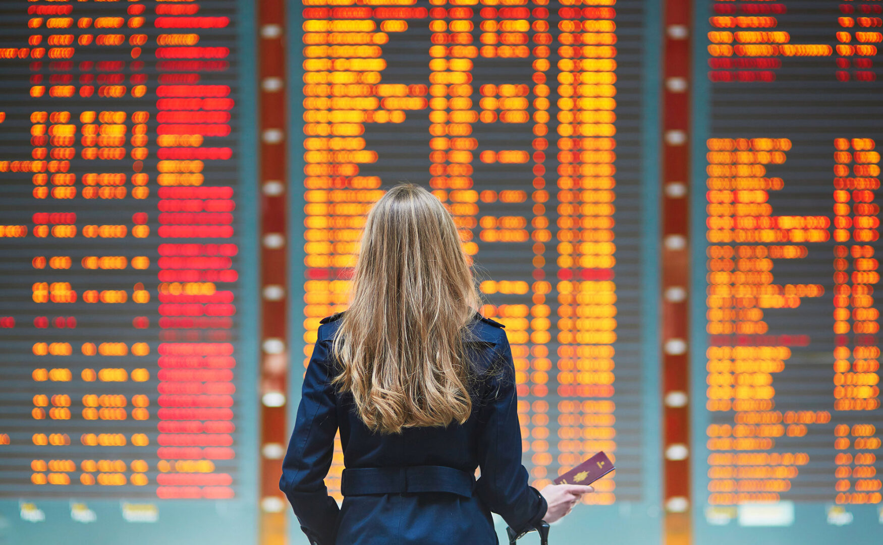 Woman traveler in front of airport departures board