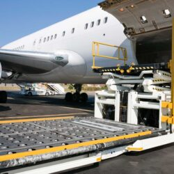 Air cargo being loaded on to plane into cargo hold.